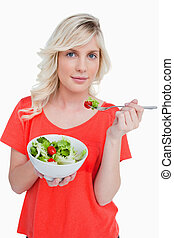 Young blonde woman eating a vegetable salad