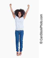 Young dynamic woman raising her arms above her head against...