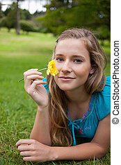 Young relaxed woman holding a beautiful yellow flower while...