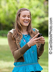 Teenage girl laughing while receiving a text on her...