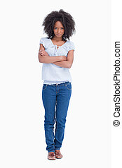 Young serious woman crossing her arms while standing upright...