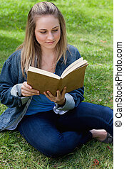 Young relaxed girl reading a book while sitting on the grass