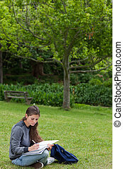 Young serious girl doing her homework while sitting on the grass in the countryside