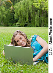 Young woman showing a great smile while lying on the side and using her laptop