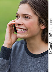 Young smiling girl calling with her cellphone while standing up