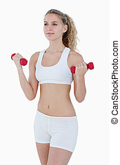 Concentrated attractive teenager lifting red weights