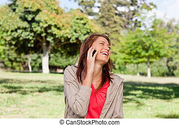 Woman laughing happily on a phone while standing in a bright grassland environment