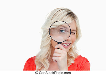 Woman looking through a magnifying glass while blinking an...