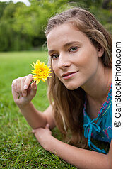 Young relaxed girl lying on the grass in the countryside...