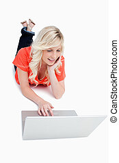 Young blonde woman lying on the floor while using a laptop