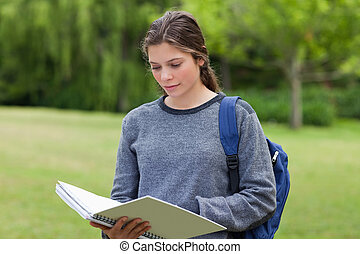 Young serious girl reading her notebook while standing upright in the countryside