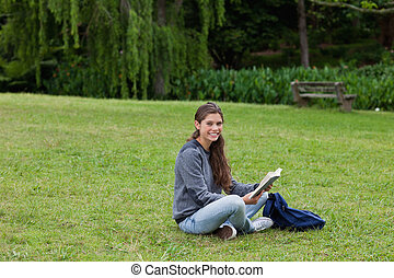 Smiling young adult reading a book while sitting...