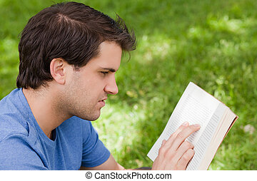 Young serious man reading a book while sitting in a park