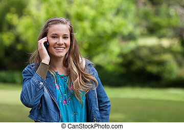 Young smiling girl talking on the phone while standing in a park