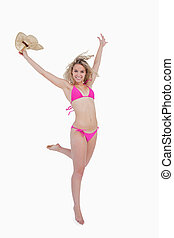 Smiling young blonde woman raising her arms while holding her ha