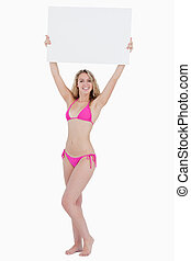 Young blonde woman raising a blank poster above her head