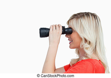 Side view of an attractive woman looking through binoculars