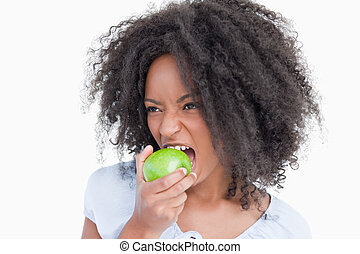 Young woman eating a green apple