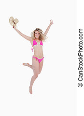 Smiling woman raising her arms while flexing her leg back against a white background