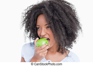 Young woman looking on the side while eating a green apple -...