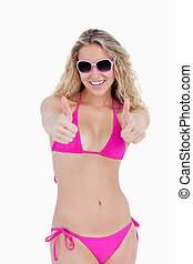 Teenage girl in beachwear putting her thumbs up against a white background