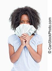 Young curly woman hiding her face behind a fan of dollars -...