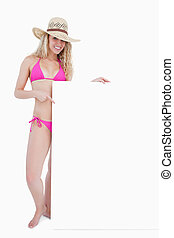 Smiling teenager in beachwear holding a blank poster
