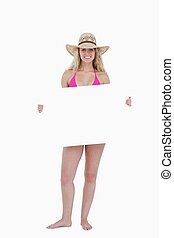 Smiling teenager in a pink swimsuit holding a blank poster
