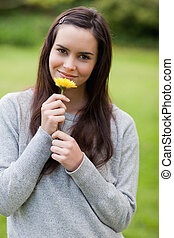 Young peaceful woman smelling a yellow flower while standing...