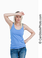 Sad blonde woman putting her hand on forehead against a...