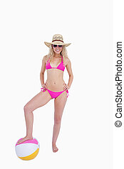 Attractive young woman putting her hands on her hips while placing foot on a beach ball