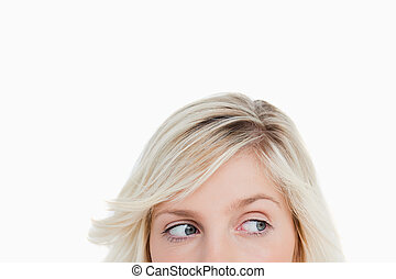 Eyes of a young blonde woman looking on the side against a...