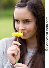 Relaxed young girl standing in a public garden while holding...