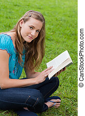 Young relaxed girl reading a book while sitting cross-legged on the grass in a park