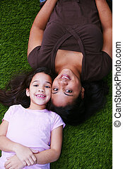 Mother with Child - Young girl sitting in the grass with her...