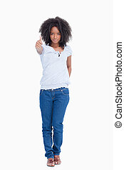 Young woman seriously standing upright with her thumbs up and a hand on her back