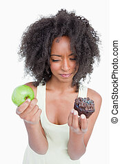 Young woman hesitating between a muffin and an apple against...