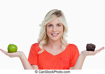 Woman showing a great smile while holding a chocolate muffin and a green apple