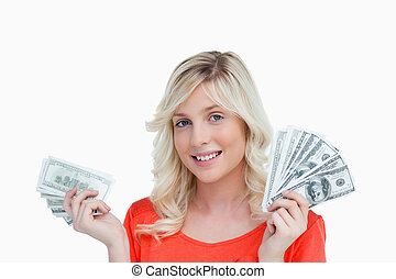 Woman showing a great smile while holding two fans of dollar not