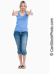 Blonde woman standing upright while placing her thumbs up