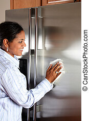 Woman Cleaning Refrigerator - Woman cleaning her stainless...
