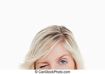 Upper part of the face of a fair-haired woman blinking an...
