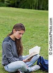 Young woman crossing her legs while reading a book - Young...