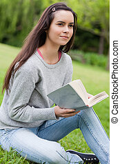 Thoughtful young girl holding a book while sitting on the grass in the countryside