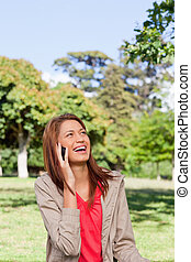 Woman laughing on the phone while looking towards the sun -...