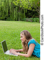 Side view of a young student using her laptop while lying on...