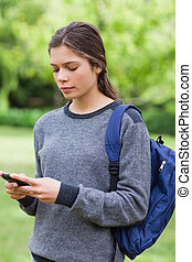 Young serious girl sending a text with her cellphone while standing in the countryside