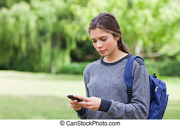 Young calm girl using her mobile phone to send a text while...