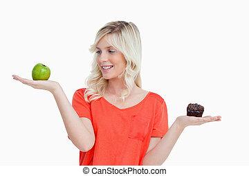 Young woman imitating a balance to choose between a fruit...