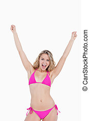 Young attractive woman in beachwear raising her arms against a white background